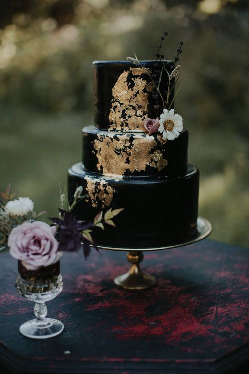 a black wedding cake decorated with gold leaf and a white bloom