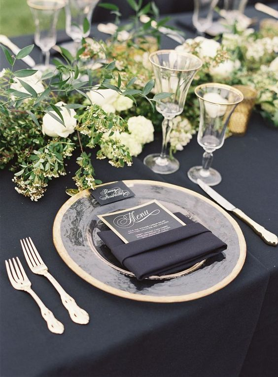a chic black and gold wedding table setting with greenery and white blooms