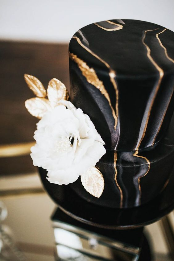 a marble black and gold wedding cake with a large white and gold sugar bloom