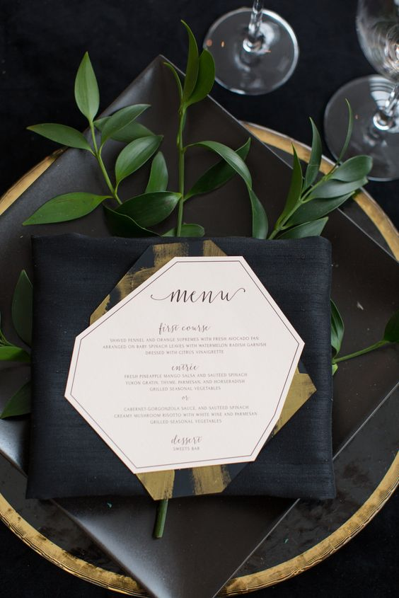 a modern place setting with a black charger with a gold edge and some greenery