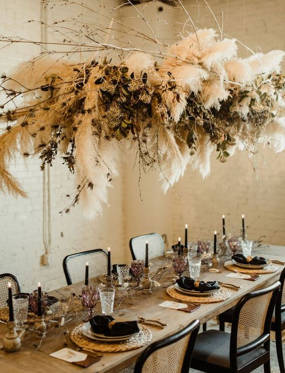 a boho chic tablescape with black napkins and candles, wicker chargers, geometric touches, dried florals and pampas grass