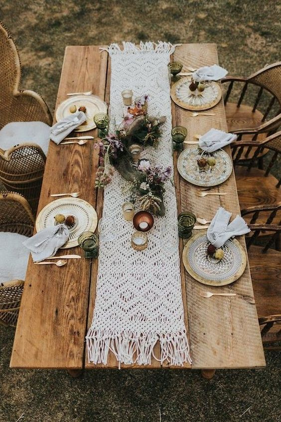 a boho chic wedding table setting with a macrame table runner, dyed napkins, lush florals and greenery, gilded plates and candles