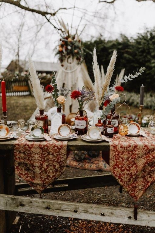 a boho table setting with printed runners, vintage tea cups, pampas grass, blooms and vintage touches