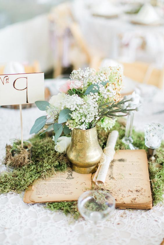 a chic vintage-inspired wedding centerpiece with moss, an open book, a gilded vase and blooms plus a table number