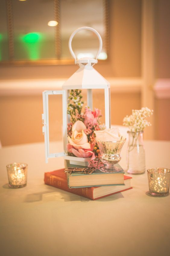 a couple of books, a glass with a white rose and a white lantern filled with fresh flowers for an elegant vintage centerpiece