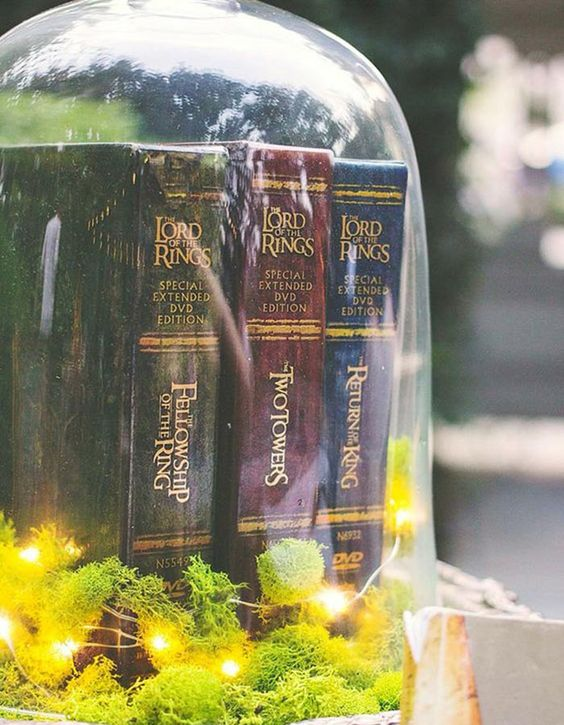 a large cloche with moss, LED lights and LOTR books is a cool idea for a themed wedding