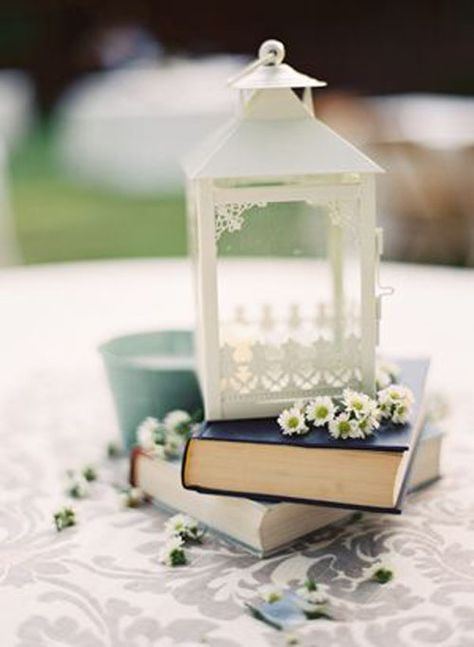 a simple wedding centerpiece of a couple of books, some chamelias, a white lantern