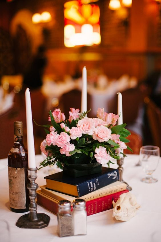 a stack of books, a black vase with pink flowers and candles around to compose a beautiful vintage wedding centerpiece