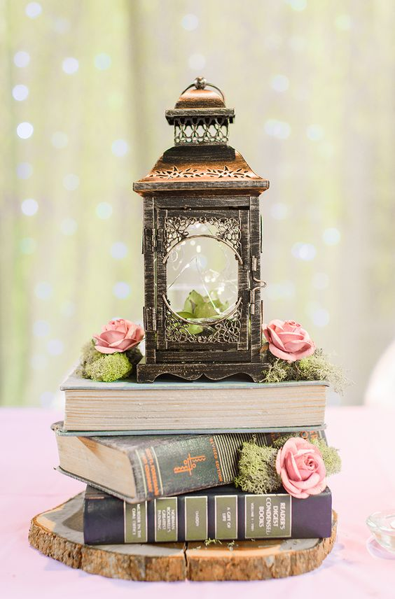a stack of books, moss, pink roses and a large vintage lantern with a succulent inside looks rustic and vintage at the same time