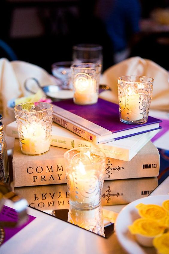 a stack of books on a mirror tray with candles in glass candle holders is a laconic and very budget-friendly idea