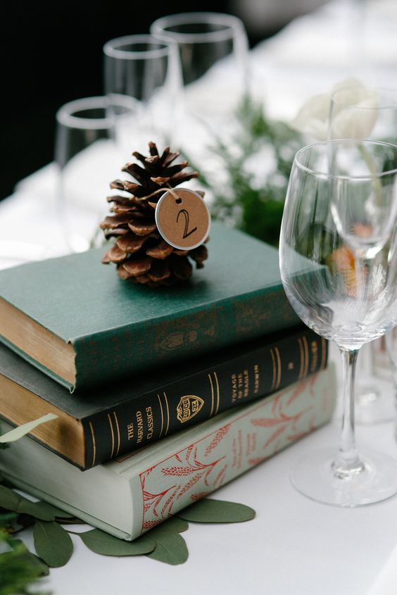 a stack of vintage books, a pinecone with a table number tag for a winter wedding centerpiece