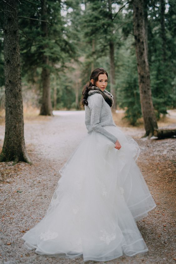 a grey comfy sweater over a princess-style wedding dress and a faux fur scarf looks very contrasting