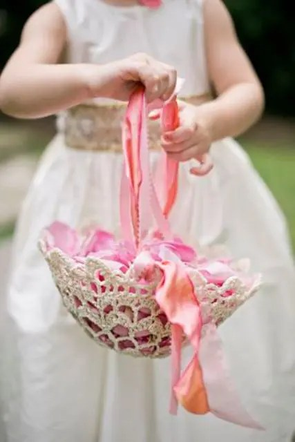 a doily and colorful ribbon basket with colorful petals is a basket with a vintage feel