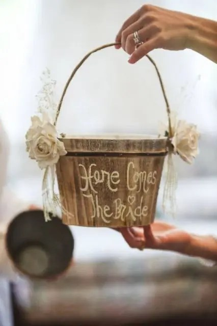 a wooden bucket decorated with fabric blooms, ribbons and calligraphy for a rustic wedding