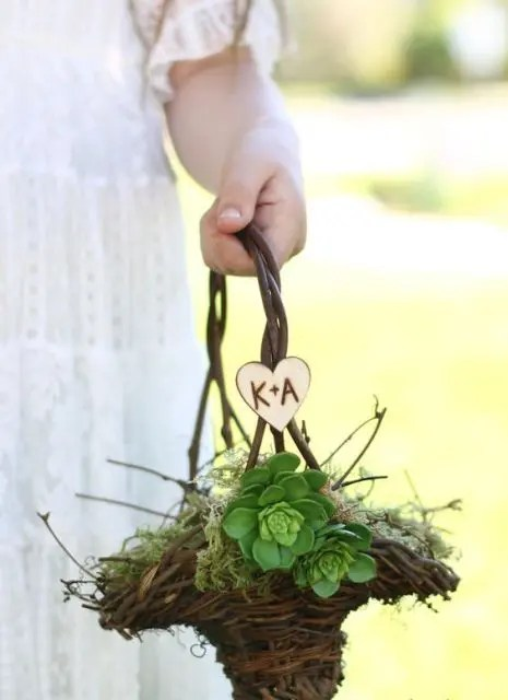 a vine basket with moss, succulents and a heart with monograms for a rustic wedding