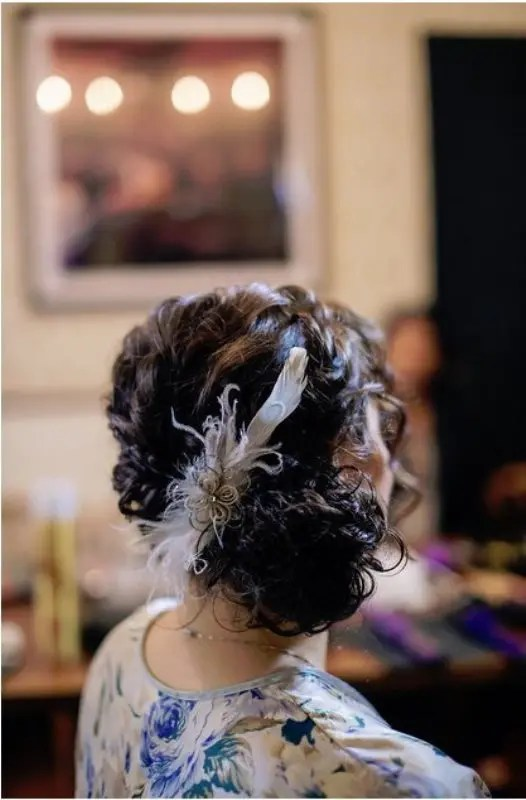 a curly side low bun accented with a feather hairpiece is great for art deco weddings