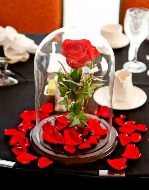 a cloche with a single red rose and petal around is a chic and bright Disney themed wedding centerpiece
