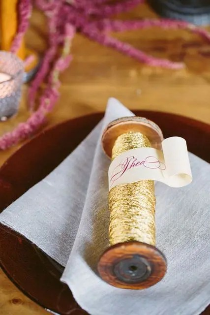 gold yarn and ribbons with a ribbon with the guest's name is a veyr creative idea of a place card