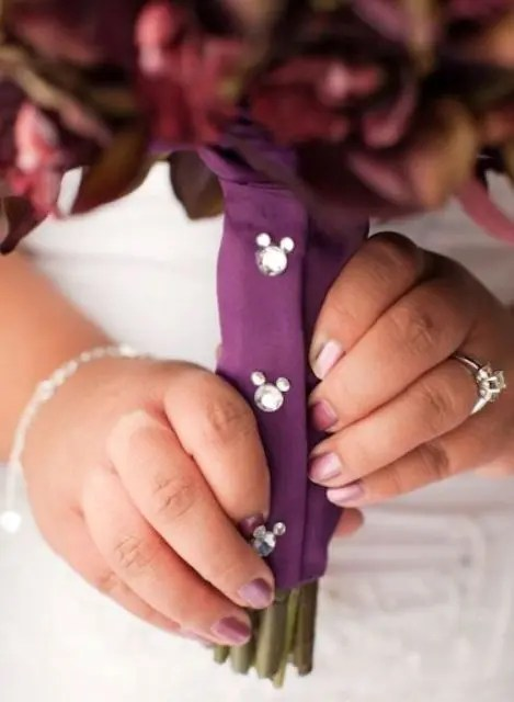 a purple bouquet wrap with rhinestone Micckey Mouse heads for decor is a fun and small touch