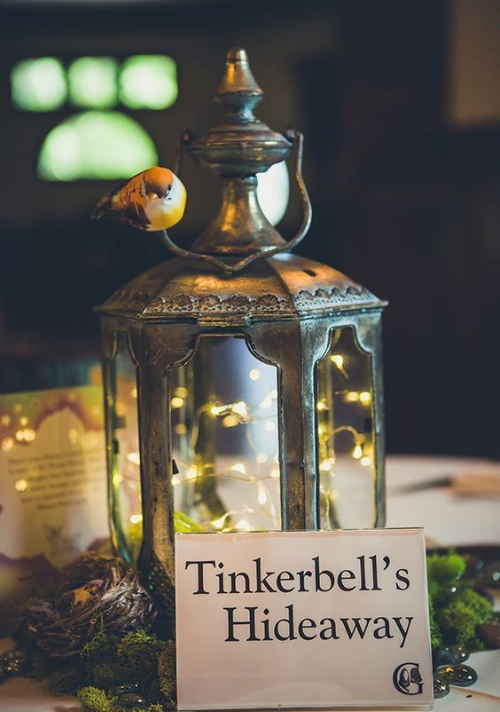 Tinkerbell's Hideaway wedding centerpiece of a metal lantern with LEDs, moss, a little nest and a birdie on it