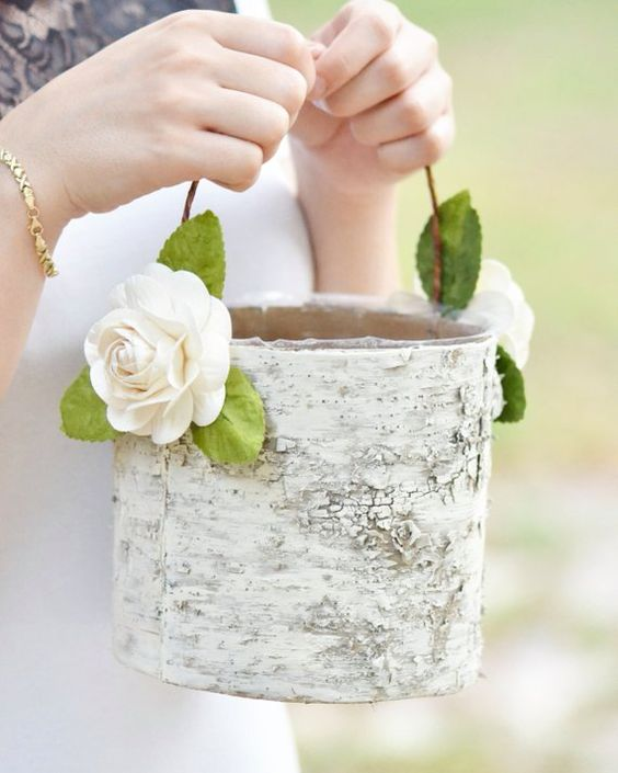 a basket made of tree bark and decorated with fabric blooms and greenery is a nice fit for a rustic wedding