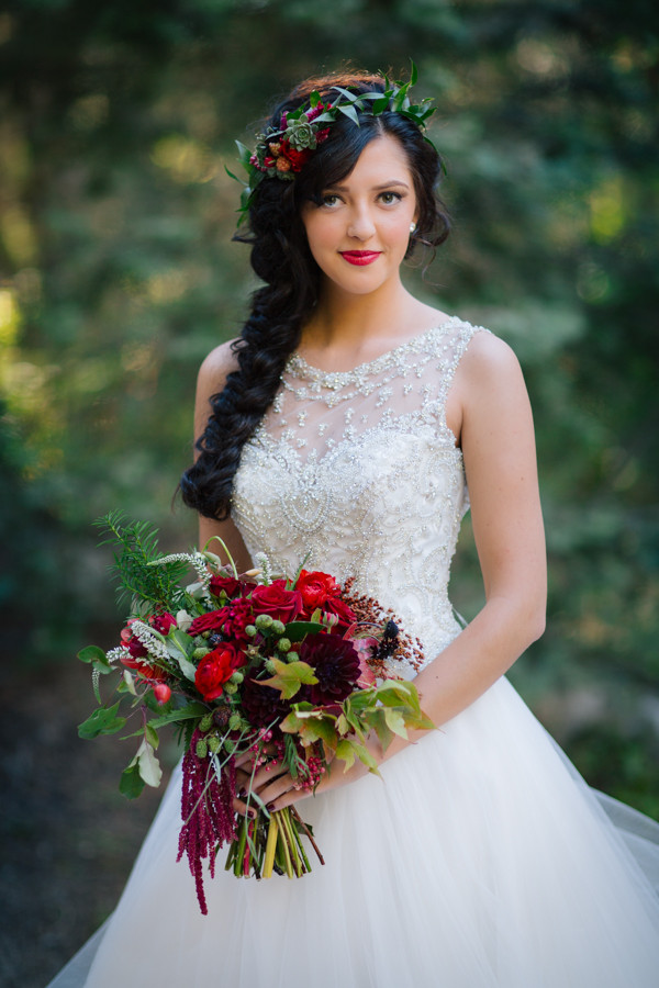 a beautiful Snow White bridal look with an embellished ballgown, a long braid with a floral and greenery crown plus a bold bouquet