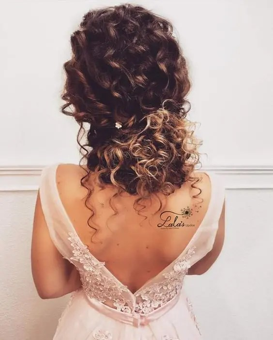 a curly low updo with locks down and twists with a single floral hairpin will add romance to your look