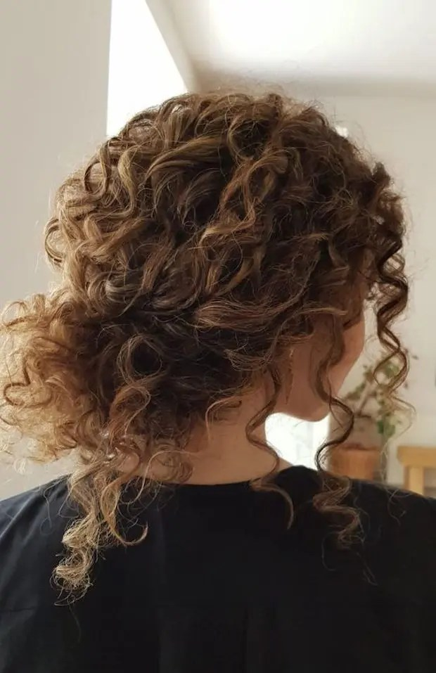 a curly messy low bun with bangs is a timeless idea for girls with curls - looks very pretty and relaxed