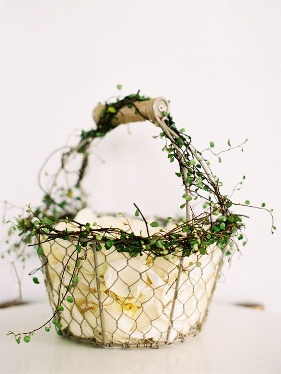 a wire basket decorated with some greenery is a cool idea with a rustic feel