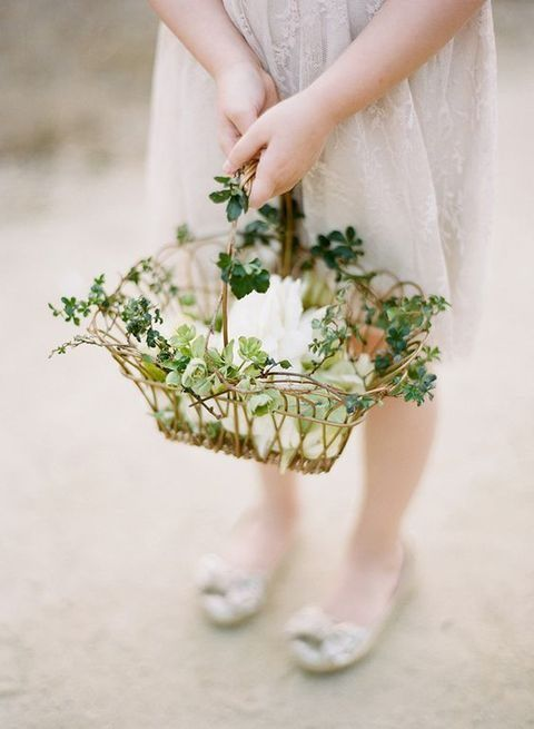 a woven see-through basket decorated with greenery and with petals inside