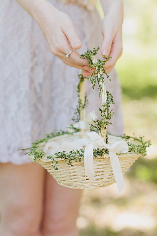an ivory basket with greenery and a white ribbon bow plus petals inside is a beautiful and refined idea