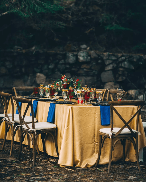 the Beauty and the Beast inspired tablescape done in gold, bold blue and deep red plus gold rim glasses and bright florals