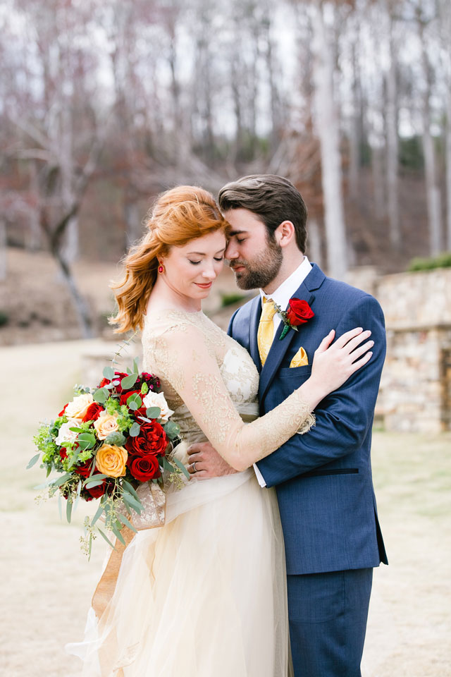 the groom wearing a blue suit with a yellow tie and handkerchief, a red rose boutonniere to match the Beauty and the Beast groom's look
