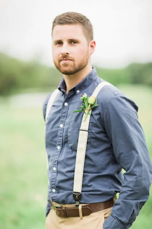 a simple barn look with a chambray shirt, tan pants and suspenders and a floral boutonniere
