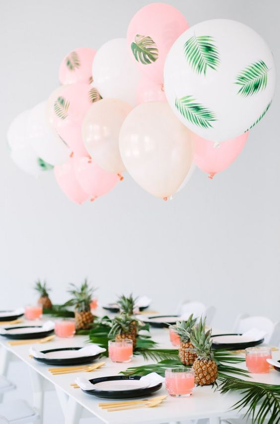 a fun tropical bridal shower tablescape with a tropical leaf table runner, pineapples, gold cutlery and pink and white balloons