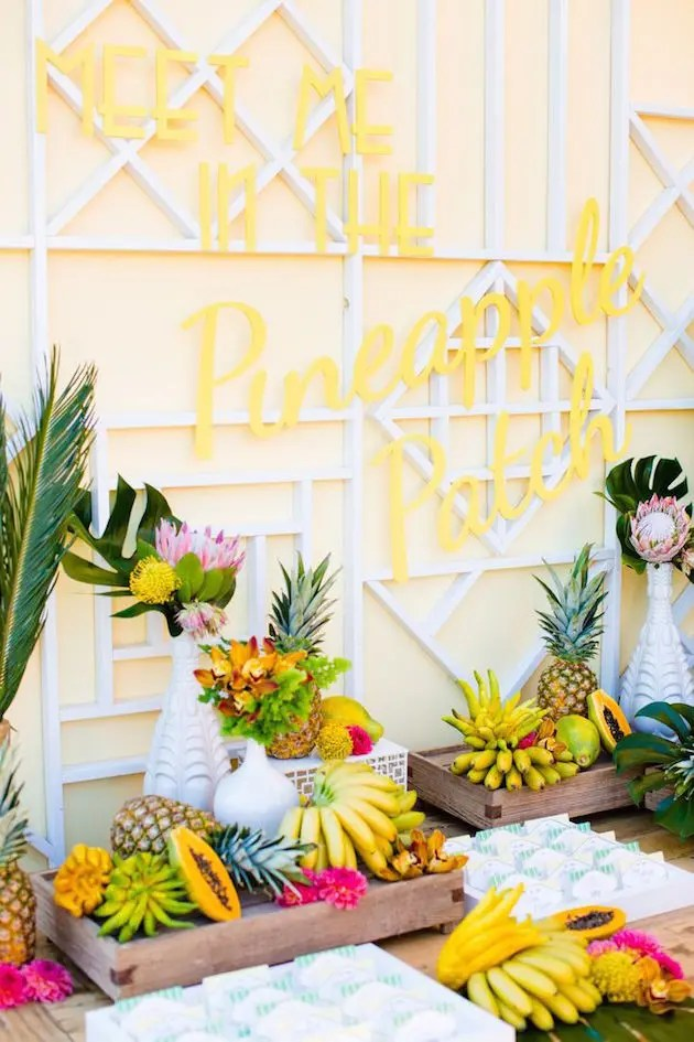 a tropical fruit table decorated with tropical leaves with a yellow neon sign over it