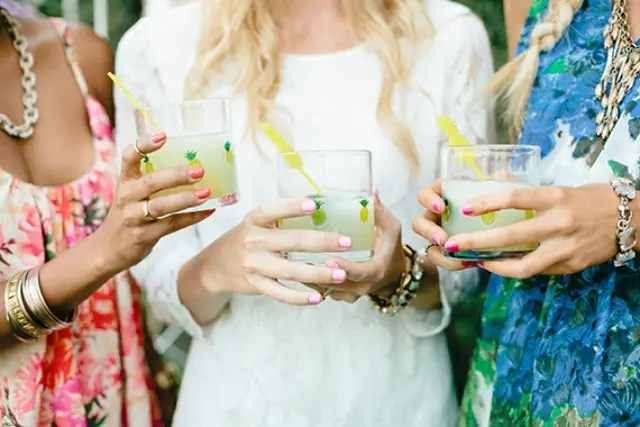 glasses with pineapple stickers and bright yellow cocktail stirrers for a tropical bridal shower