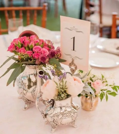 a bright and fun centerpiece of a silver teapot and coffee pit used as vases for blush and hot pink blooms and a table number