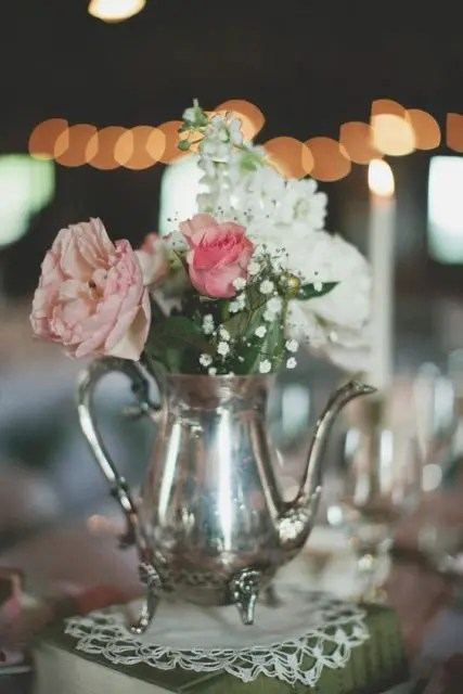 a vintage book with a doily, a silver teapot and white, blush and dusty pink blooms