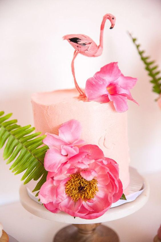 a blush bridal shower cake with large pink blooms, a leaf and a flamingo topper for fun