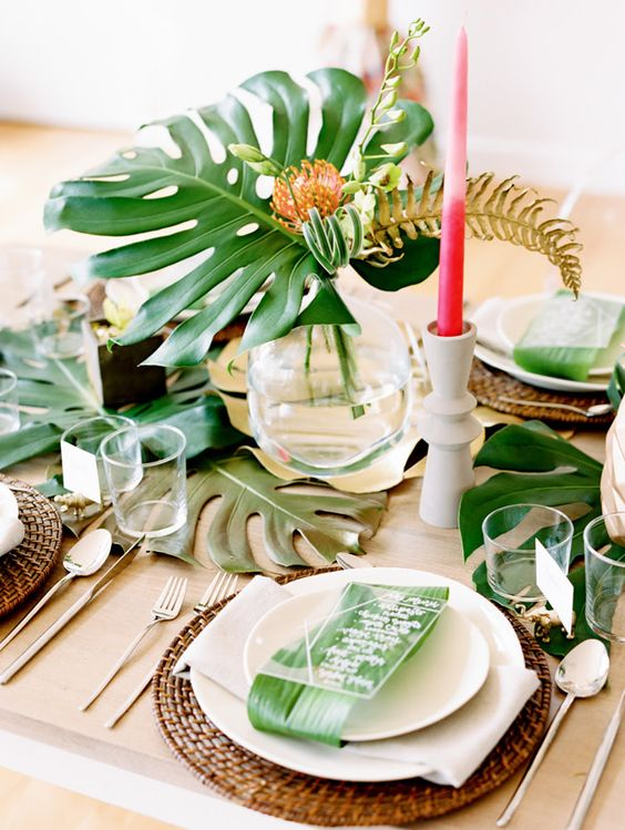 a chic tropcial bridal shower tablescape with wicker chargers, pink candles, monstera leaves and clear glasses looks very modern