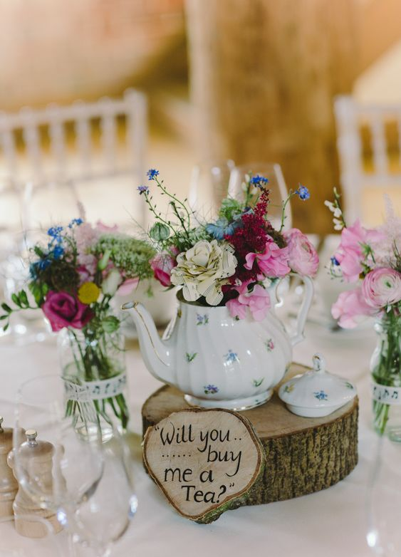 a cool teapot wedding centerpiece of a wood slice, a wood sign, a florla teapot with bright blooms, glasses and bright flowers