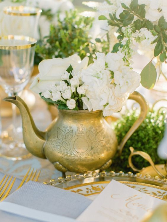 a gilded teapot with neutral blooms and greenery is a chic vintage and elegant wedding centerpiece