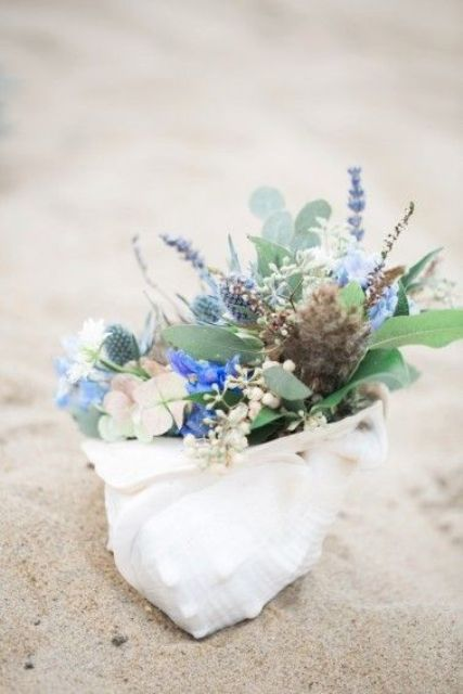 a seashell decoration with fresh blue blooms, greenery and thistles is a cute idea of a bridal shower centerpiece