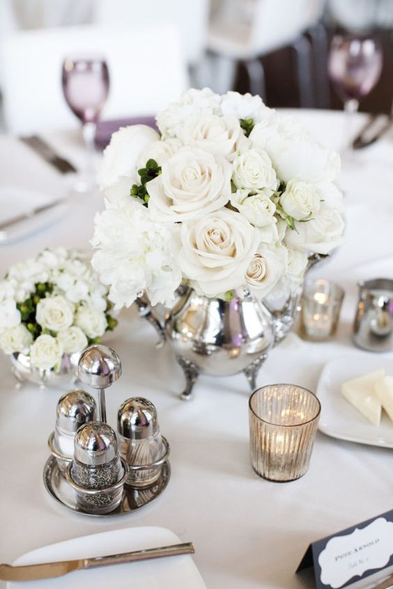 a silver teapot with white roses and mercure glass candle holders is pure elegance