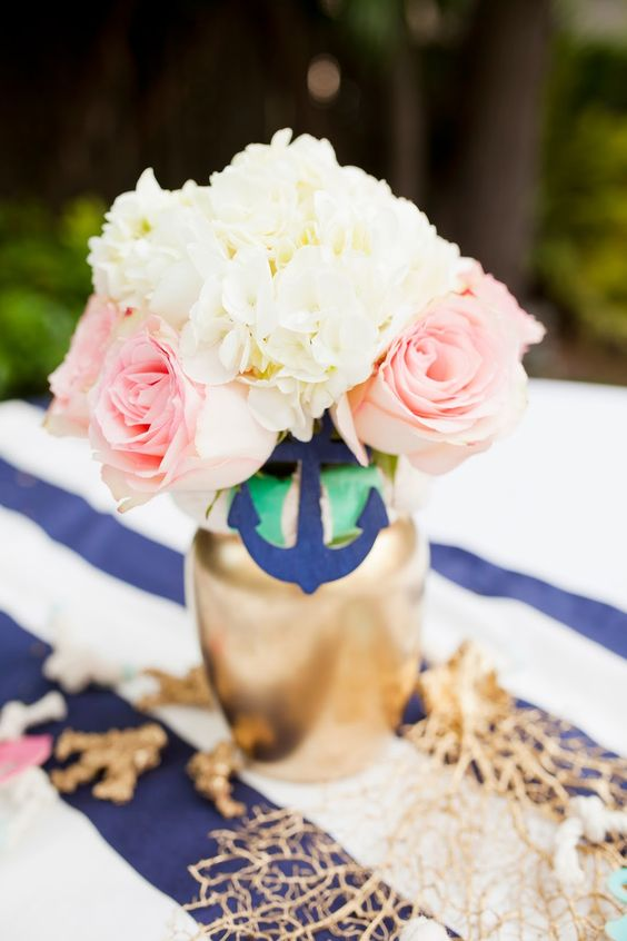 a simple bridal shower centerpiece with a gilded vase, a navy anchor, neutral and pink blooms plus net