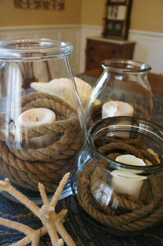 a simple centerpiece with large jars and candles wrapped with rope and coral and shells for a nautical bridal shower