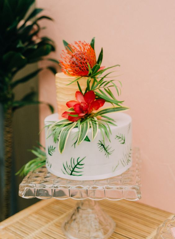 a tropical bridal shower cake with a gold tier, a white tier with greenery, blooms and greenery