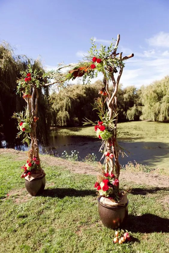 rustic living arch with bold red flowers
