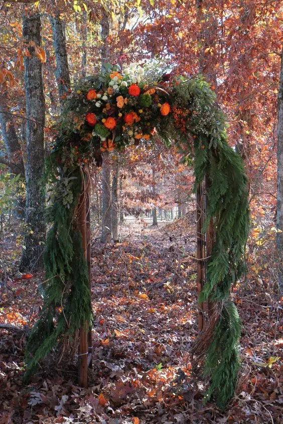 fir branches arch with flowers on top